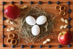 Foodstuff composition with eggs on hay, berries and apples. 3 eggs on hay, 2 red apples, crackers, peanuts and blueberries on a wooden cutting board Royalty Free Stock Images