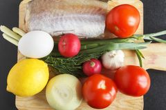 Foodstuffs for healthy balanced dish from various vegetables, egg and fish on closeup. Fresh organic tomatoes, rich in vitamins ra. Dish and garlic. Top view royalty free stock photography