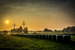 A foogy morning with hay bales during sunrise royalty free stock images