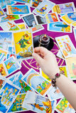 The Fool. Tarot card held in hand. Tarot card The Fool held in hand. Background: tarot cards and magic candle stock photo