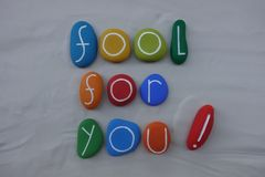 Fool for you. Passion love words composed whit colorful sea stones over white sand royalty free illustration