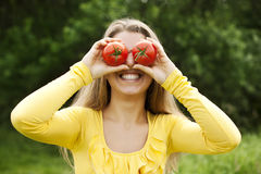 Fooling around with tomatoes. Young woman fooling around with tomatoes Royalty Free Stock Photography
