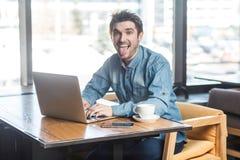 Fooling rond Het portret van knappe kinderachtige positieve gebaarde jonge freelancer in jeansoverhemd zit in koffie en stock foto's