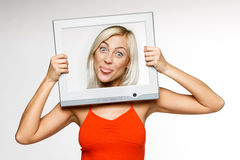Fooling woman looking through computer frame Stock Photo