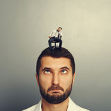 Foolish man with small bored man on the head Royalty Free Stock Image