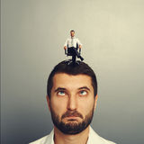 Foolish man with small smiley man on the head Royalty Free Stock Photos