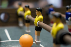 Foosball game yellow team close up. Photo of entertaining foosball game table Royalty Free Stock Photos