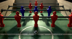 Foosball Table. At ground level with a soccer ball in front of the red team ready to kick off a soccer match stock image