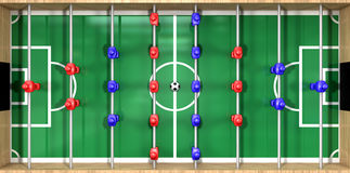 Foosball Table Top View. A direct top view of a wooden foosball table showing a blue and red team on a green marked pitch on an isolated white background Royalty Free Stock Photo