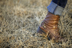 A foot. In boot walking through grasses Royalty Free Stock Photo