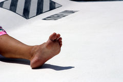 Foot aboard. A woman's foot relaxed aboard a catamaran sailboat stock image
