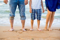 Foot adults and a child on the beach Stock Photos