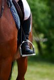 Foot of the athlete in a stirrup. Astride a horse Royalty Free Stock Image