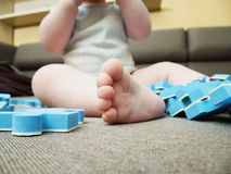 Foot of baby with puzzle pieces on sofa in the living room at home stock photography
