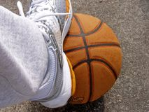 Foot on Ball. Tennis shoe on top of basketball Royalty Free Stock Images