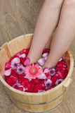 Foot bath with flowers in spa salon. A young woman enjoy foot bath with flowers in spa salon, indoors Stock Photos