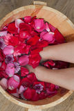 Foot bath with flowers in spa salon. A young woman enjoy foot bath with flowers in spa salon, indoors Royalty Free Stock Photo