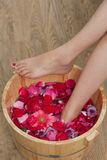 Foot bath with flowers in spa salon. A young woman enjoy foot bath with flowers in spa salon, indoors Royalty Free Stock Image