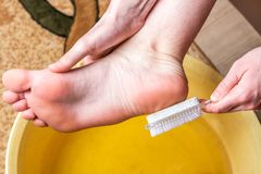 Foot baths. Care for dry skin on feet and heels. Using pedicure pumice tools and a brush. royalty free stock images