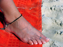 Foot on the beach. Detail of a bare female foot over an orange towel and sand Royalty Free Stock Images