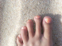 Foot on a beach with painted toe nails. Foot with long toes and painted nails on sand Stock Images