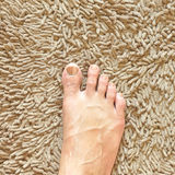 Foot on beige carpet Royalty Free Stock Photo