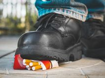 Foot in a black boot crushes a pack of cigarettes stock photo