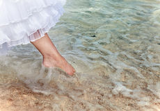 The foot of the bride touches water in the sea Stock Photo