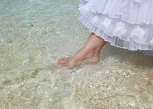 Foot of the bride touches water in the sea Stock Photos