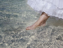 The foot of the bride touches water in the sea Royalty Free Stock Photos