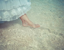 Foot of the bride touches water in the sea,with a retro effect Stock Photos