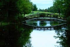 Foot Bridge. A small foot bridge over a pond Stock Image