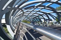 At the foot of the bridge. Angular view of the Rolex open canopy bridge in Geneva. curves lines shadows cars bikes pedestrian passage crossing Am Fuß der Br