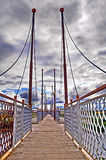 Foot-bridge with cloudy sky. The old foot bridge with the cloudy sky Royalty Free Stock Photography
