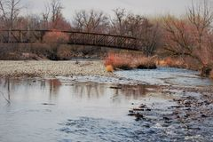 A foot bridge crossing the Boise River. In winter. Trees are bare and the water is low royalty free stock photos