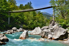 Foot bridge over a mountain river with blue-green cold water, big stones and green forest around Stock Image