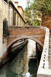 Foot Bridge over Narrow Canal, Venice, Italy. Small Arched Foot Bridge over Narrow Canal Lined with Houses, Venice, Italy Royalty Free Stock Photos