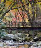 Foot Bridge over rocky stream in the Smoky Mountains. Foot Bridge over rocky stream with autumn leaves falling in the smoky mountains of Tennessee Stock Photography