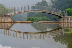 Foot bridge over a small pond with reflection in the water Stock Photography