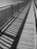 Foot bridge Over The Water. View of foot bridge (showing shadows) over a lake. Image is black & white Royalty Free Stock Photos