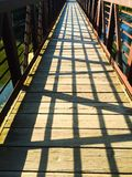 Foot Bridge with Shadows. A walking bridge with an interesting criss- pattern of shadows in the evening light stock images