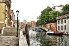 Foot Bridge Spanning Venetian Canal in Urban Area Royalty Free Stock Photography