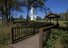 Foot bridge and White Church. Stock Photo