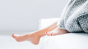 Foot care treatment wellness beauty relaxation. Foot care concept. Treatment and wellness. Beauty and relaxation. Female legs peeking out from blanket. Copy stock photography