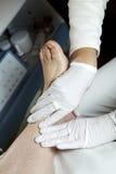 Foot care - Massage - Reflexology. Podiatrist gives a women a leg and foot reflexology royalty free stock photos