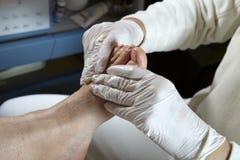 Foot care - Massage - Reflexology. Podiatrist gives a women a leg and foot reflexology stock photos
