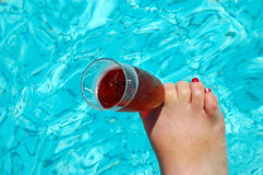 Foot with champagne glass. A white female foot of a caucasian lady with red nailpolish holding a champagne glass with sparkling wine in a swimming-pool Royalty Free Stock Image