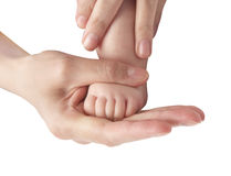 Foot of the child in a hand of mum. Stock Photos