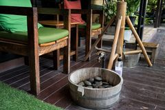 Foot clean before massage at spa. Outdoor chairs to clean foot by water, soap, and natural rocks before Thai massage in spa salon Royalty Free Stock Images