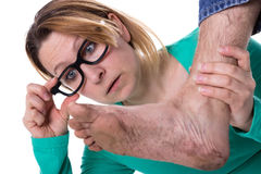 Foot covered with dirt. Woman with glasses is astonished about a dirty foot Stock Images